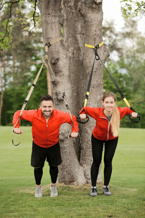 Portrait of sport man and woman training in park with suspension trainer sling. Happy couple in red jackets looking at camera while doing fitness exercises.