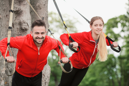 Happy sport man and woman training in park with suspension trainer sling preparing for jogging long distances.