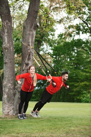 Sport couple training in green park with suspension trainer sling. Fitness man and woman in red jackets preparing for sportrs competitions.