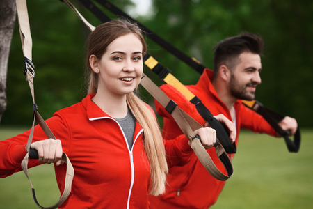 Closeup picture of beautiful sport or fitness woman training with suspension trainer sling with her colleague man in green park.