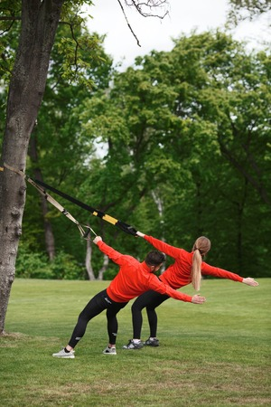 Group of man and woman exercising with suspension trainer in green park on fresh air. Sport couple doing simultaneous exercises.