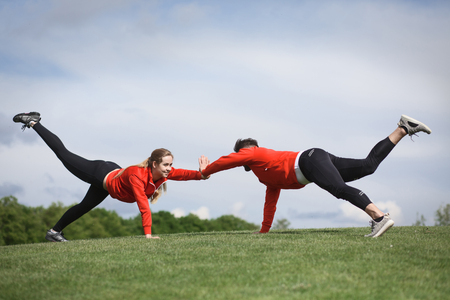 Sport man and woman in red jackets training in green park or forest. Couple of fitness people doing sport exercises outdoors.