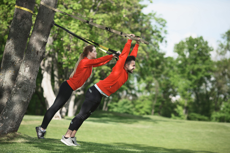 Sport man and woman training with suspension trainer sling in park. Man as personal trainer showing his partner how to keep fit.