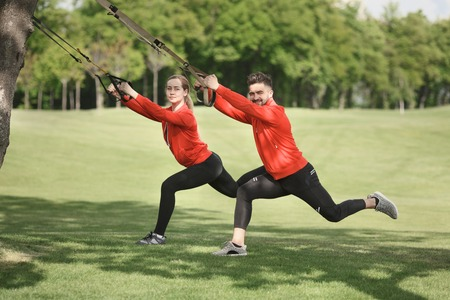 Group of sport people exercising with suspension trainer in green park. Happy man and woman in red jackets looking at camera.