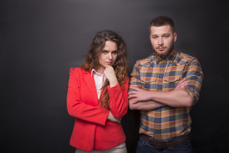 Portrait of confident business man and woman posing in studio. Freelancers posing with their arms crossed over black background.