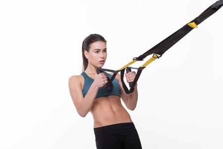Beautiful woman training with suspension trainer sling or suspension straps in studio. Studio shot.