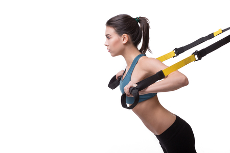 Beautiful woman exercising with suspension straps alone in studio.