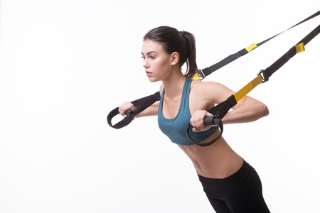 beautiful woman exercising with suspension straps alone in studio. isolated on white background