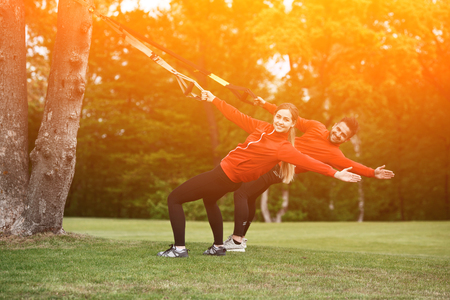 Sport man and woman training in park with TRX