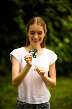 Fidget spinner in hands of young pretty girl.