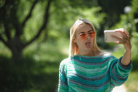 Photo pour Stylish girl in sunglasses taking selfie. Gorgeous woman with light blonde hair wearing warm sweater taking pictures via her phone and sticking her tongue out. - image libre de droit