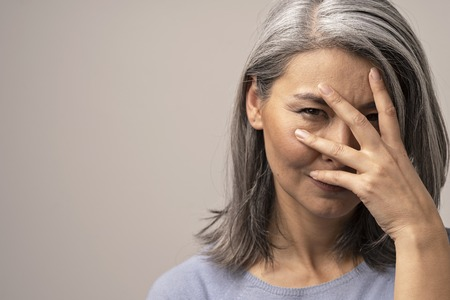 Photo pour Asian Woman With Grey Hair Squints Her Eyes And Covers Her Face With A Hand. Beautiful Woman Covering Her Face And Peeping Through Fingers At Camera. Horizontal Shot Of Middle-Aged Woman s Portrait At The Right Side Of A Photo - image libre de droit