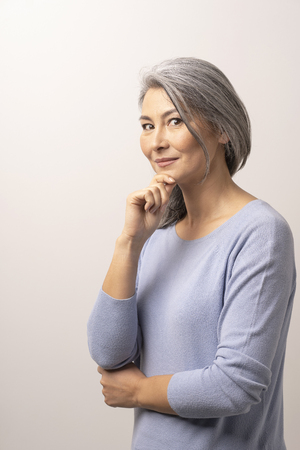 Photo pour Charming Woman Touching Her Chin With One Hand. Happy Asian With Grey Hair Lightly Smiles And Delicately Touches Her Chin With Hand. Studio Photoshoot. - image libre de droit