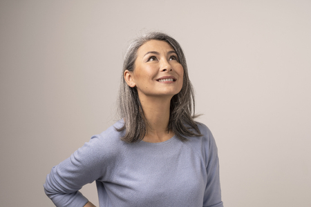 Foto de Smiling Woman With Grey Smiles And Looks Up. Attractive Middle-Aged Asian Woman Looking Up And Smiling. Studio. Portrait. - Imagen libre de derechos