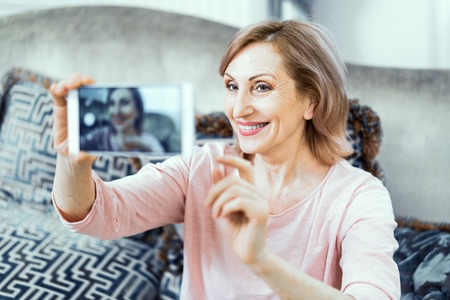Foto de Elderly Woman at Home in the Living Room with a Phone in Her Hands. A Woman Wants to Take a Picture of Herself on the Phone. On the Face of the Womans Sweet Smile. Close Up Shot. - Imagen libre de derechos
