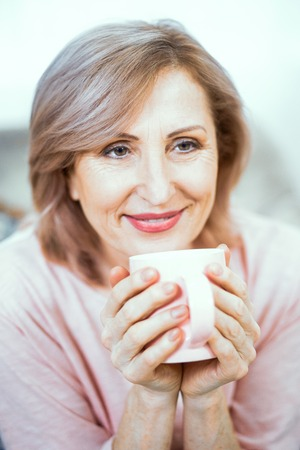 Photo pour Charming Smiling Senior Woman With Cup Of Tea. Beautiful Woman Gently Smiles While Holding A Cup Of Coffee. Portrait. Closeup. - image libre de droit