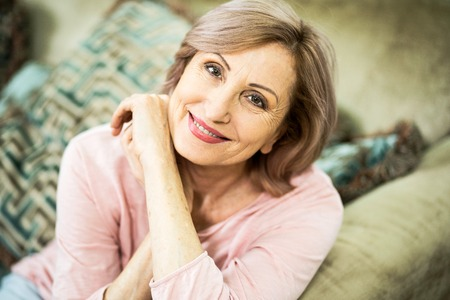 Photo pour Woman of European Appearance Resting at Home in the Living Room. In Appearance Woman are Over 50 Years Old. The Woman Gently Smiles Into the Frame. Close Up Shot. - image libre de droit