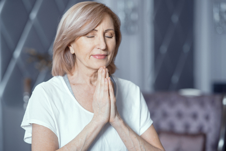Photo for Peaceful Woman With Closed Eyes Does Namaste With Prayer Hands. Charming Woman Holds Her Palms Pressed Together Praying. Portrait. - Royalty Free Image