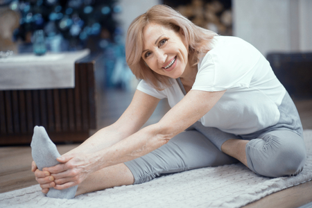 Photo pour Concetrated Woman Stretches Her Feet Touching Her Feet. Mature Woman Does Yoga Exersice Reaching For Her Toes. Healthy Lifestyle. Stretching. - image libre de droit