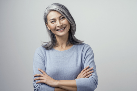 Foto de Attractive Optimistic Grey-Haired Mature Asian Woman Smiles Widely In Studio and Crosses Her Hands, Head Tilted. Hands and Shoulders Tonned Portrait On White Background. - Imagen libre de derechos
