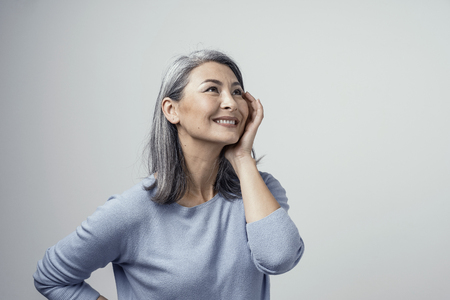 Sexy Middle-Aged Woman Grey Hairstyle in Sudio. She Touches her Cheek and Raises Eyes Up Dreamily .Half-Turned Studio Shot.