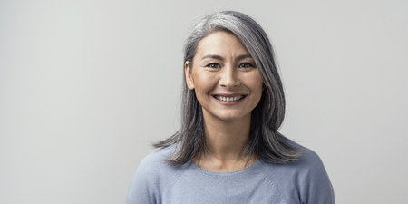 Foto de Beautiful Mature Asian Woman Smiles Broadly In Studio. Right Side Tonned Closed-Up Portrait. White Background. - Imagen libre de derechos