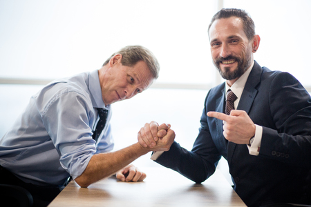 Photo pour Two Businessmen Doing Arm Wrestling. Office Interior With Big Window. Relaxing In Office Concept. - image libre de droit