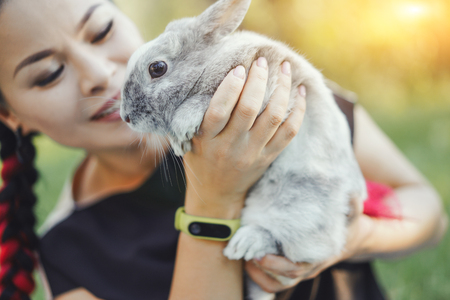 Photo for Close-up of Pretty Asian Hugging Bunny on Summer Nature - Royalty Free Image