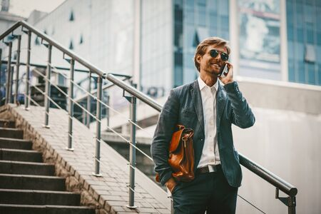 Photo pour Young brown-haired businessman or trainee standing outside of business centr in a blue sute and sunglasses and talking on a phone. Man standing at the stairs of business center - image libre de droit
