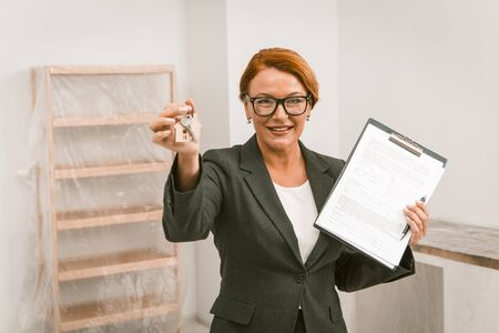 Photo pour Realtor Proposing To Sign An Agreement For Apartment Rent, Camera Focused On Face, Woman Realtor Stnading In The Room With Keys And Agreement In Her Hands, Toned Image - image libre de droit