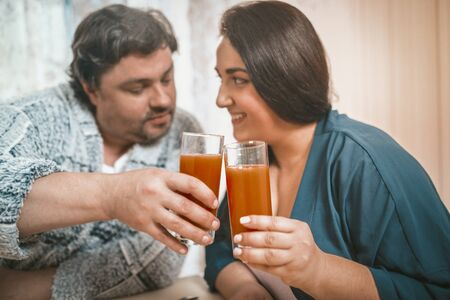 Photo for Body Positive Man And Woman Clinking With Glasses Of Orange Juice, Caucasian Couple Casual Clothing Flirting And Joining With Glasses While Sitting At Home - Royalty Free Image