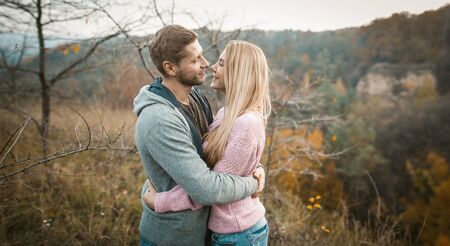 Photo pour Lovely Couple Of Travelers Stands Embracing On Cliff Edge Outdoors, Smiling Man And Woman Are Hugging And Looking At Each Other While Standing Against Background Of Autumn Nature - image libre de droit