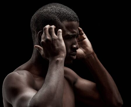Photo pour Afro-American man feels headache or stress. Profile portrait of naked dark-skinned man expressing exhaustion. He massages his head with hands isolated on black background. - image libre de droit