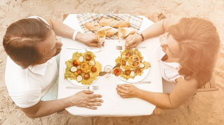 Foto de Middle-aged couple in love sitting at a table with salad and glasses of white wine on a sandy beach, Happy man and a woman looking each other, High angle view, Toned image. - Imagen libre de derechos