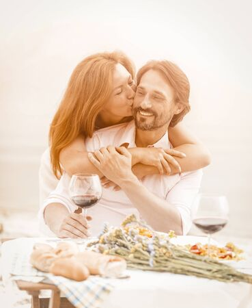 Foto de Happy middle-aged couple resting in a beach cafe, a beautiful woman tenderly kisses her man hugging his shoulders, a man and a woman eat and drink wine in the fresh air. Toned image. - Imagen libre de derechos