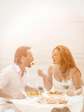 Photo pour Happy couple rest in beach cafe. Mature woman feeding her man. Care for loved ones concept. Romantic concept. Tinted image. - image libre de droit