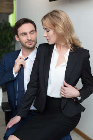 Photo pour Adorable blonde flirts with boss in office, sitting on his lap. Businesswoman seducing coworker at office. Love affair at job. Foreplay at workplace. - image libre de droit