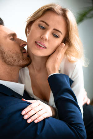 Photo for Passionate couple have workplace romance. Lovers coworkers wearing formalwear hugging and kissing in office. - Royalty Free Image