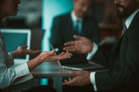 Photo for Businessman and businesswoman gesturing with hands while conversation during meeting in office. Sign language concept. Close up shot. Tinted image. - Royalty Free Image
