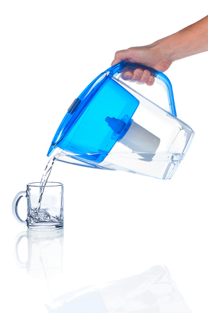 Photo pour Pouring water in glass from water filter pitcher - image libre de droit