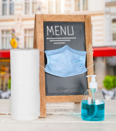 Photo pour Wooden menu blank with medical mask and hygiene products for protection from coronavirus - image libre de droit