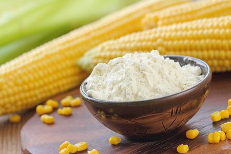 Foto für Corn flour in a bowl and corn cob on the table - Lizenzfreies Bild