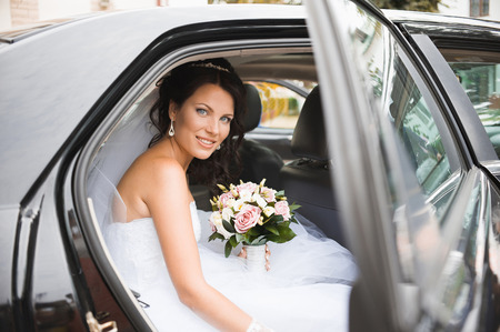 Photo pour Young bride in a wedding car. Bridal bouquet. - image libre de droit