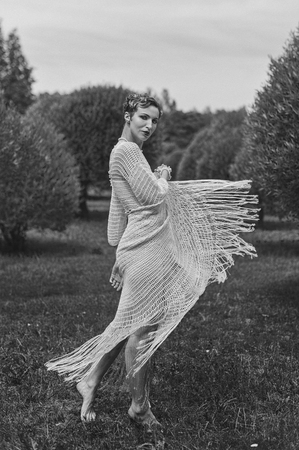 Photo for Black and white photography of young dancing woman wearing knitted long dress.  Outdoors image - Royalty Free Image