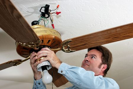 An electrician removing an old ceiling fan.  The fan was installed without a ceiling box, in violation of code.