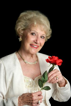 A beautiful, successful senior lady dressed in formalwear holding a red rose. She has perfect teeth.