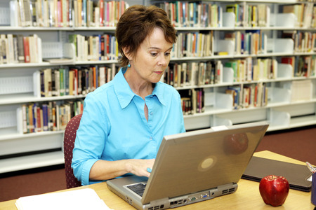 A pretty school librarian doing researh online in the media center.