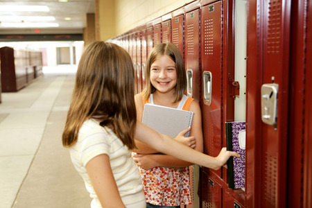 Photo pour Middle school girls gossiping at their lockers.   - image libre de droit