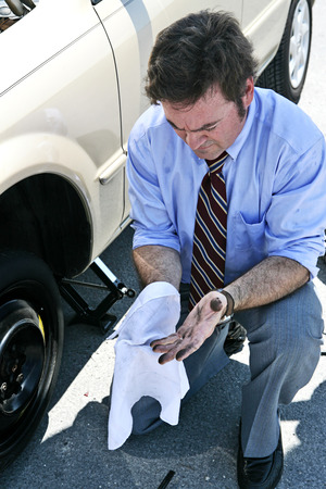 A businessman wiping his dirty hands off after changing a tire.