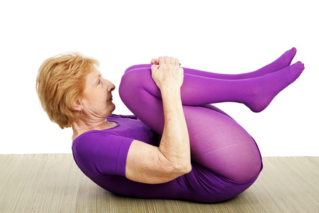 Photo for A fit flexible seventy year old woman doing a suppine yoga pose.  White background - Royalty Free Image
